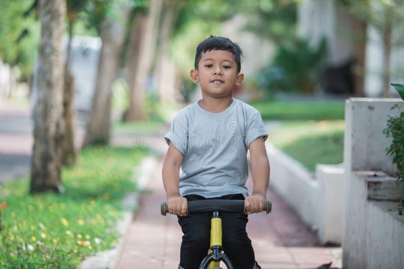 Montez un vélo utilisant la bicyclette de poussée ou d'équilibre photos libres de droits
