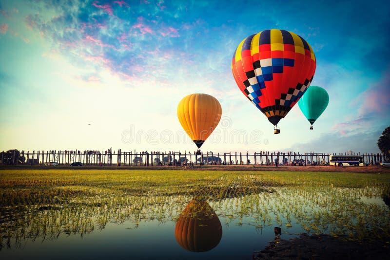 Montgolfières colorées volant au-dessus du pont d'u-bein chez la Birmanie image libre de droits