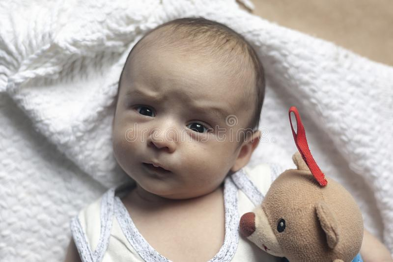 2 month baby boy lying. Close-up of adorable cute newborn baby boy of two months. Baby with suspicious face. Serious little kid. stock image