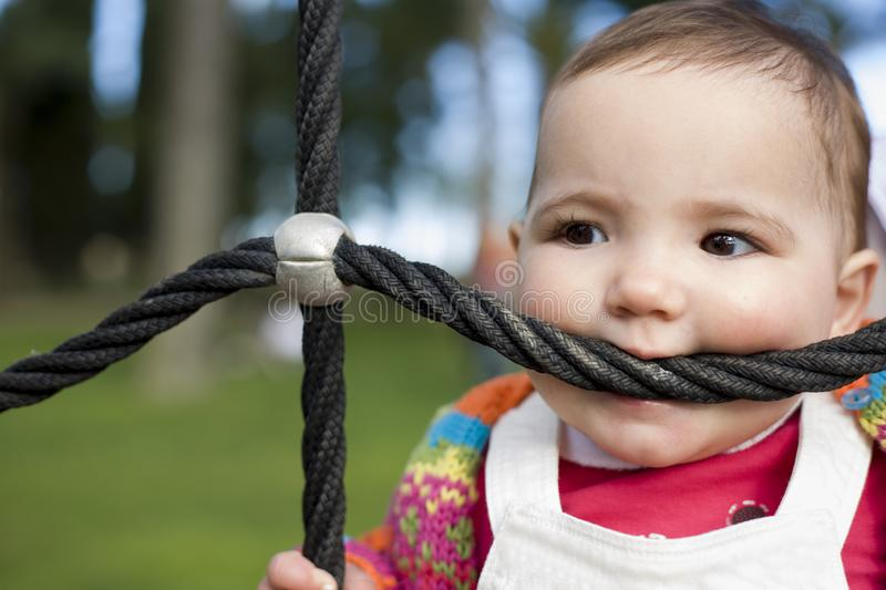 11 month baby girl bitting playground rope as it was a teether. Biting and Teething for babies concept stock photo