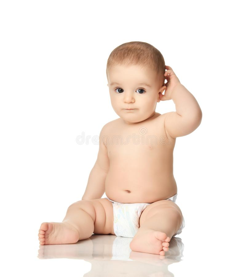 8 month infant child baby boy kid toddler sitting in diaper thinking scratch one head stock photo