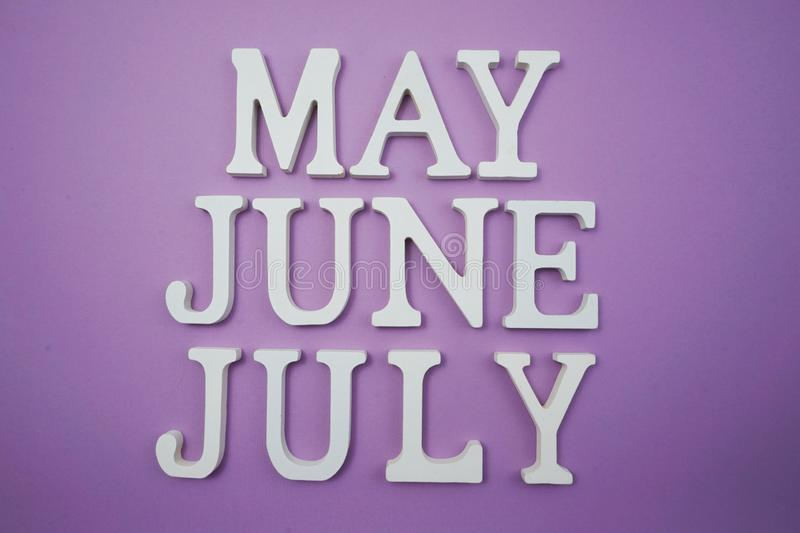 Month of May June and July alphabet letter on purple background. Top view of Month of May June and July alphabet letter on purple background stock image
