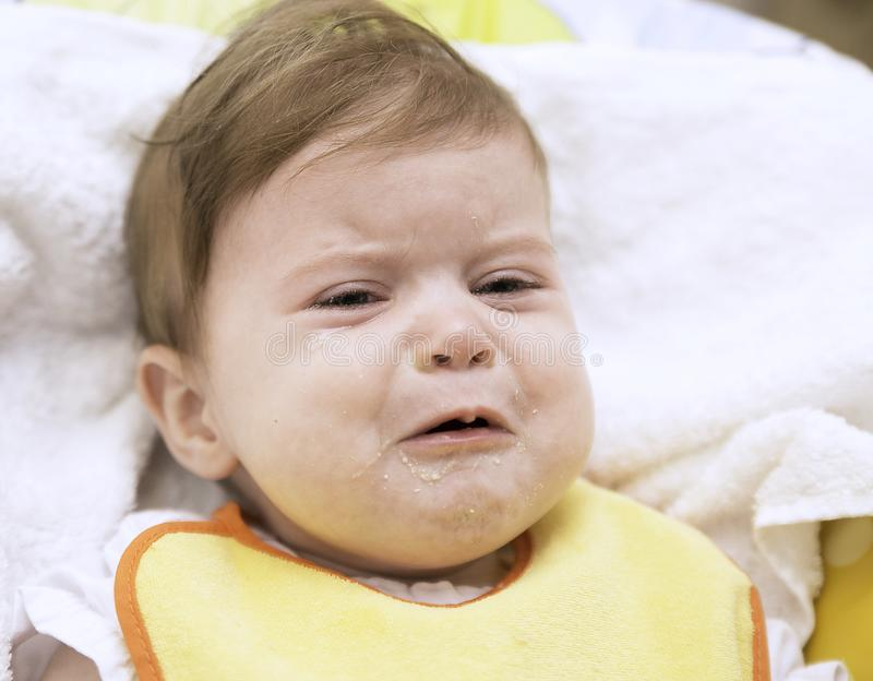The 9 month old baby is angry and refuses to eat meal. Baby feeding and baby behaviour concept. The 9 month old baby in a yellow bip is crying and refuses to eat royalty free stock images