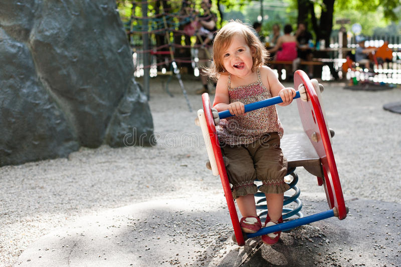 16 month old girl playing in playground stock image