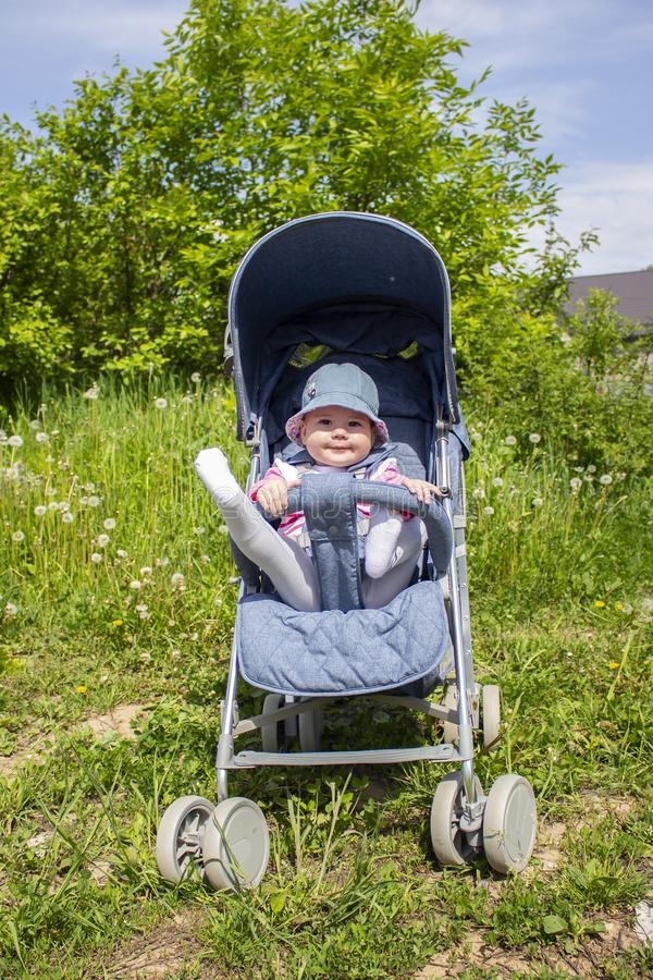 A 9 month old girl sits in a summer carriage and plays with her legs. Little smiling child in a hat on a walk, summer day royalty free stock photo
