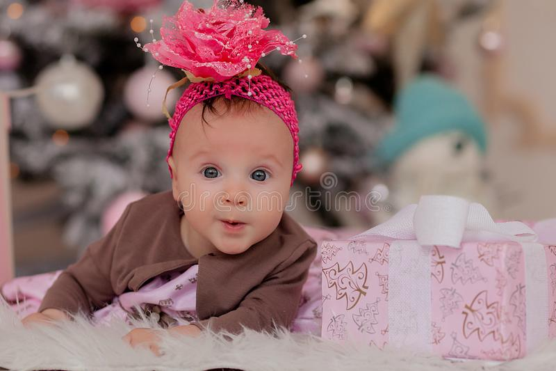 4 month old little girl under the Christmas tree. baby girl with gifts under Christmas tree royalty free stock photography