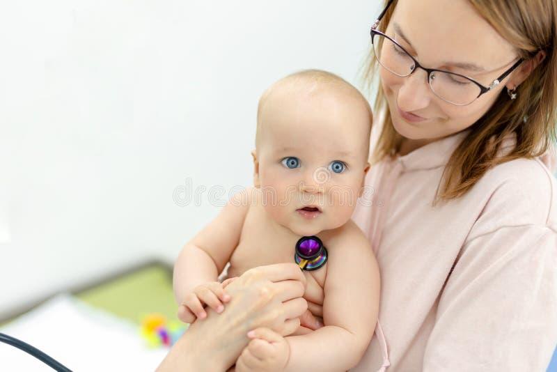 Monther держа младенца на руках на офисе докторов Педиатр делая рассмотрение маленького милого младенческого мальчика с стоковые фотографии rf