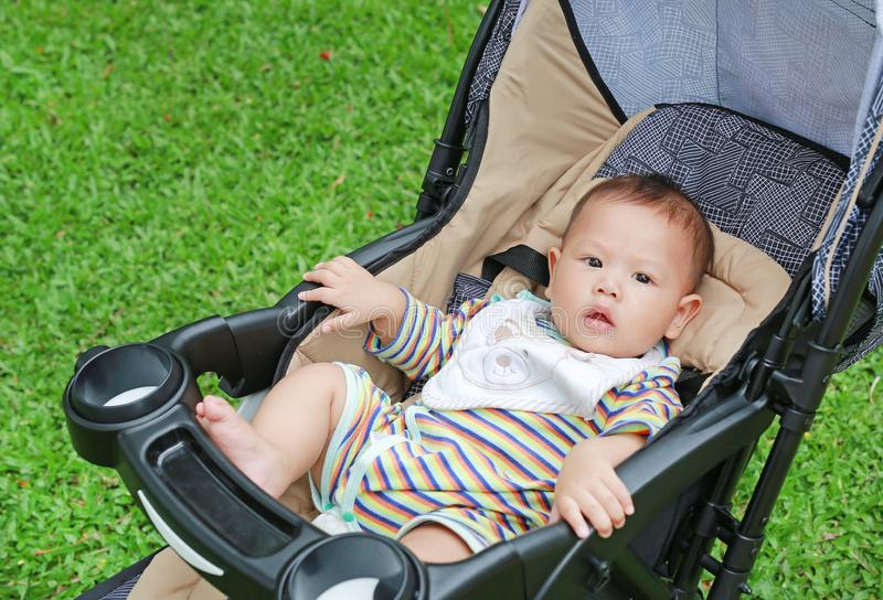 6 months little Asian baby boy sitting in the stroller at the green garden.  stock image