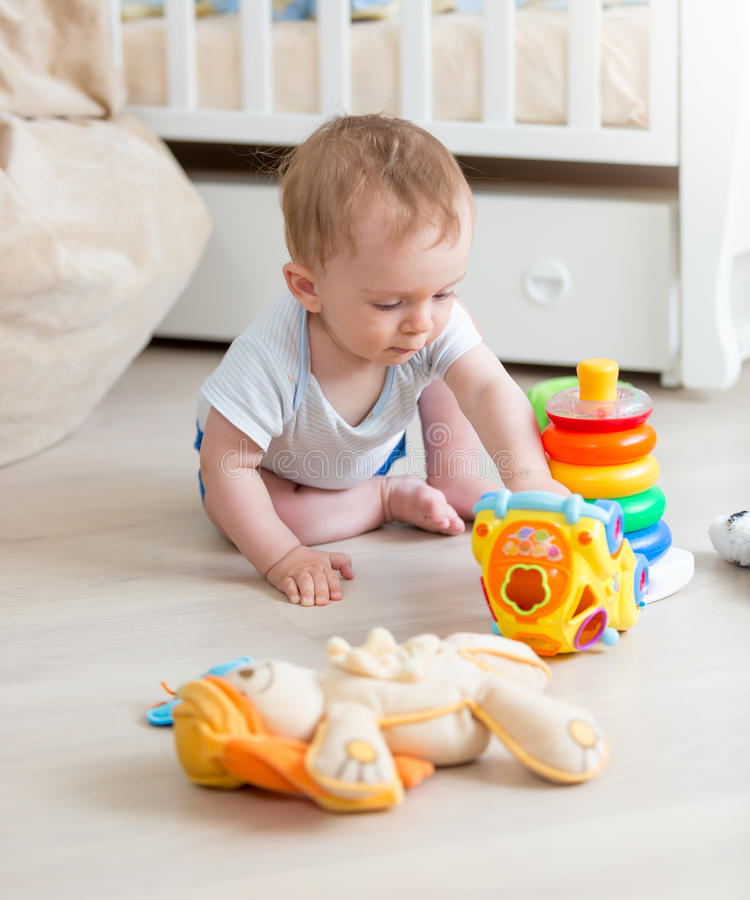 9 months old baby boy playing with colorful toys on floor at living room stock photography