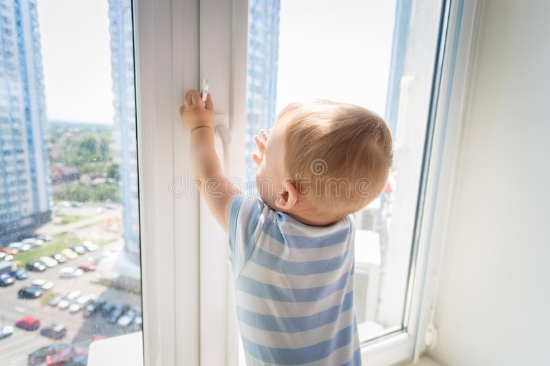 9 months old baby boy standing on windowsill and trying to open the window. Bbay in danger royalty free stock photo
