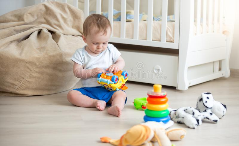 Cute 10 months old toddler boy playing with toy car on floor at bedroom. 10 months old toddler boy playing with toy car on floor at bedroom stock photography