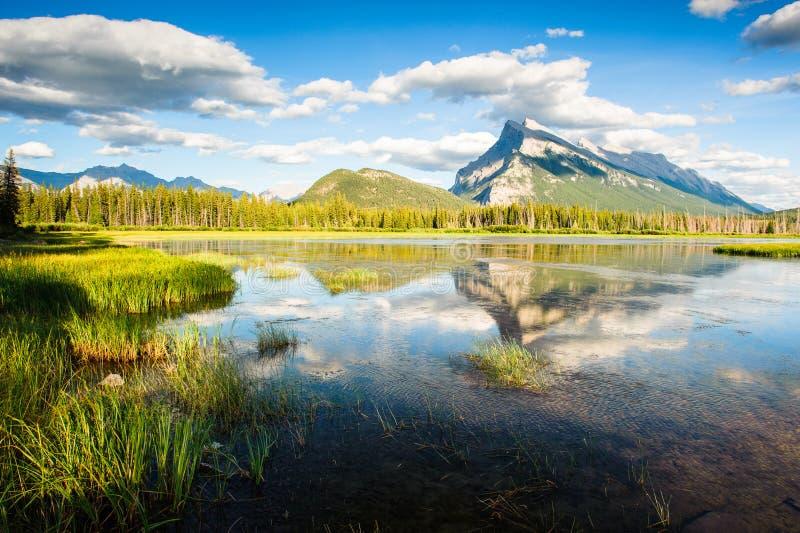 Monti Rundle con cielo blu che riflette nei laghi vermilion fotografie stock libere da diritti