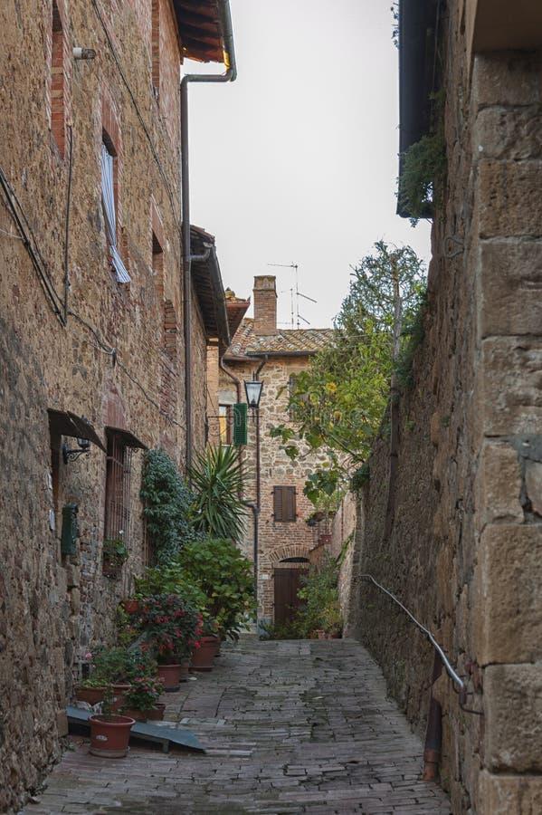 Montichiello - l'Italia, il 29 ottobre 2016: Via calma in Montichiello, Toscana con le finestre con le imposte tipiche e le vie p fotografia stock