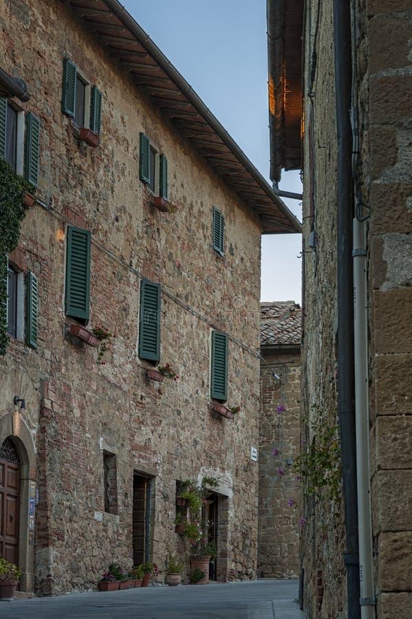 Montichiello - l'Italia, il 29 ottobre 2016: Via calma in Montichiello, Toscana con le finestre con le imposte tipiche e le vie p immagine stock libera da diritti
