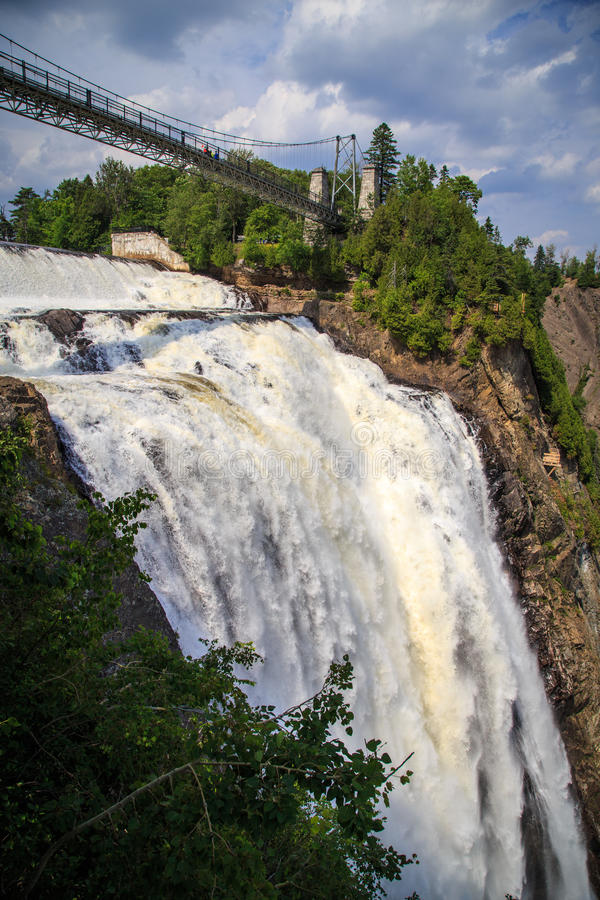 Montmorency Falls suspension bridge. The Montmorency Falls (French: Chute Montmorency) are a large waterfall on the Montmorency River in Quebec, Canada. The royalty free stock photography