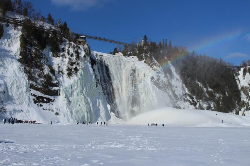 Montmorency waterfall with rainbow with snow in winter royalty free stock image