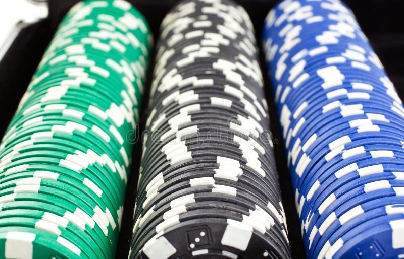 Montones de las virutas de póker en rectángulo negro foto de archivo libre de regalías
