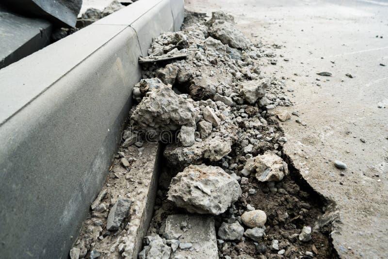 Montones del asfalto demolido que miente en la acera cerca del hoyo para instalar un encintado Asfalto quebrado Un agujero en la  fotografía de archivo