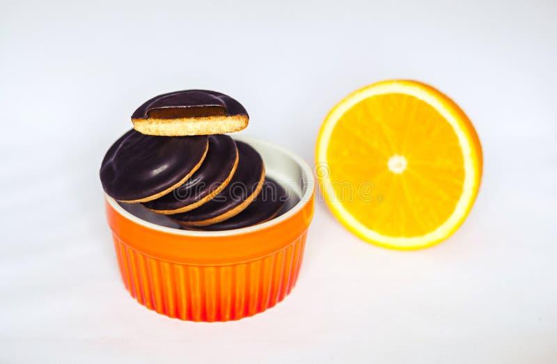 Montones del chocolate Chip Cookies con la naranja en plato de la hornada en el fondo blanco fotografía de archivo