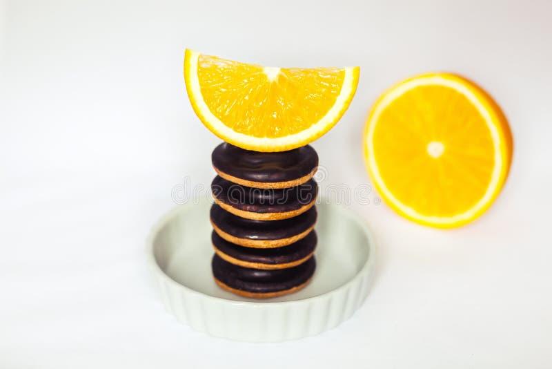 Montones del chocolate Chip Cookies con la naranja en plato de la hornada en el fondo blanco fotos de archivo libres de regalías