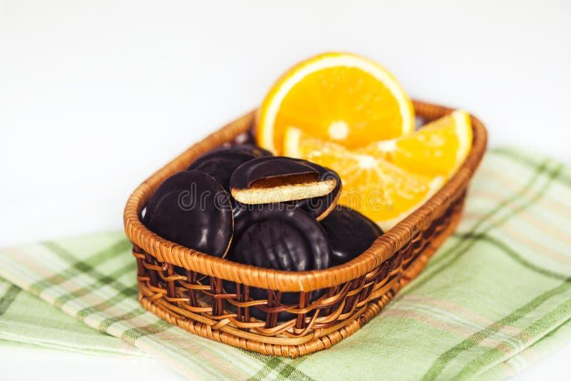 Montones del chocolate Chip Cookies con la naranja en servilleta verde y el fondo blanco imagen de archivo