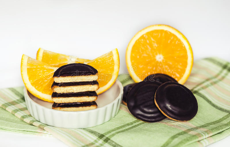 Montones del chocolate Chip Cookies con la naranja en servilleta verde y el fondo blanco fotografía de archivo