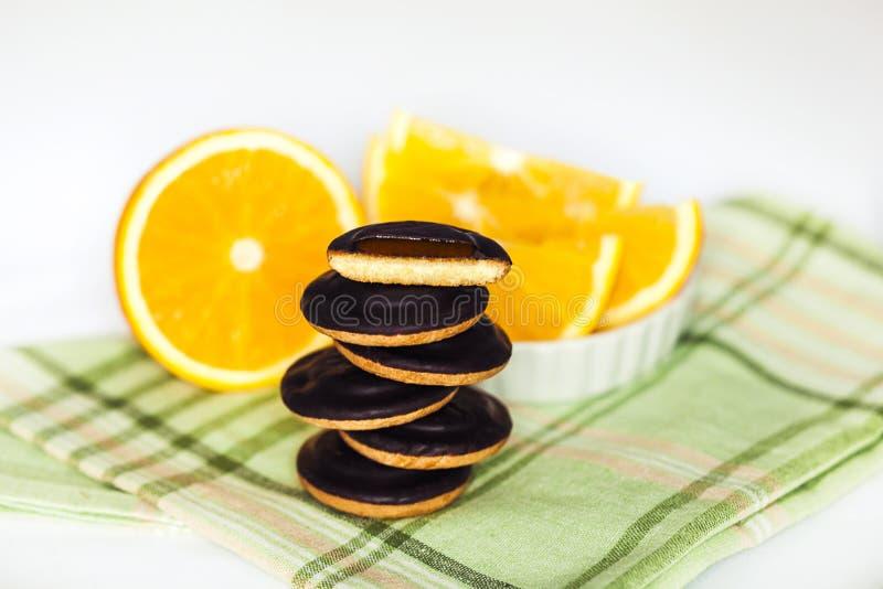 Montones del chocolate Chip Cookies con la naranja en servilleta verde y el fondo blanco fotografía de archivo libre de regalías