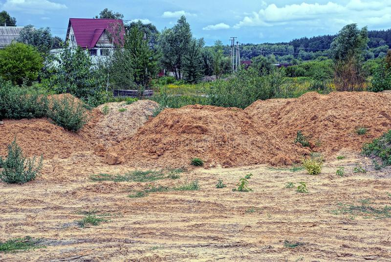 Montones grandes de la arcilla y de la tierra marrones en un matorral demasiado grande para su edad con la vegetación verde imágenes de archivo libres de regalías