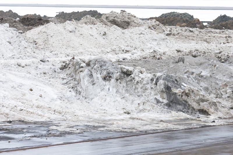 Montones grandes de la nieve sucia sacados fuera de la ciudad fotografía de archivo libre de regalías