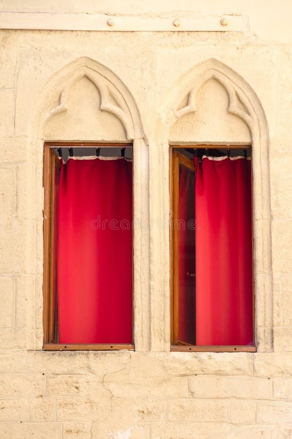 Montpellier, Francia Dos ventanas con las decoraciones y las cortinas rojas imagenes de archivo