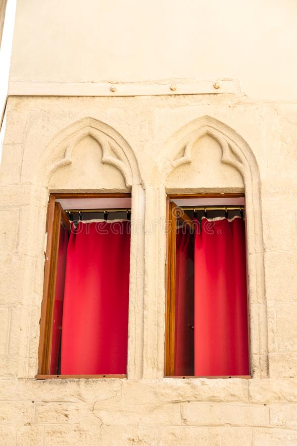 Montpellier, Frankrijk Twee vensters met decoratie en rode gordijnen stock foto's
