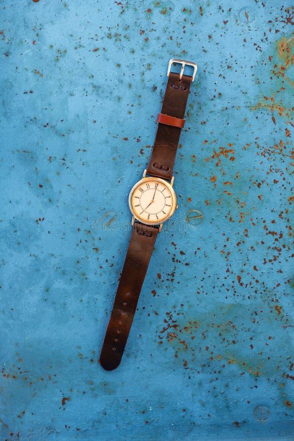 Or/montre-bracelet argentée de cru sur le banc bleu photo libre de droits