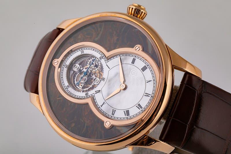 Montre-bracelet d'or masculine avec les cadrans blancs, dans le sens horaire d'or, chronomètre, sur le bracelet en cuir brun d'is images stock