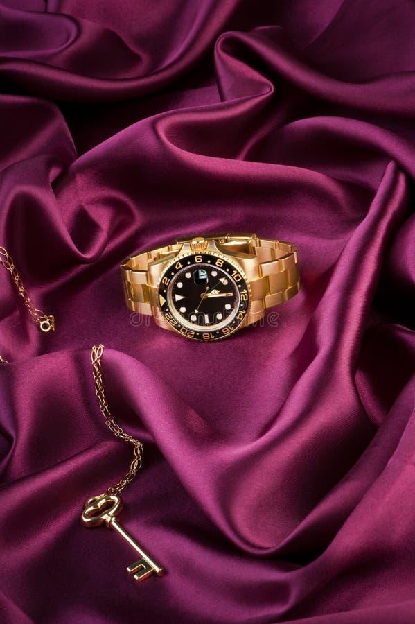 Montre-bracelet d'or se trouvant sur le tissu en soie photo libre de droits