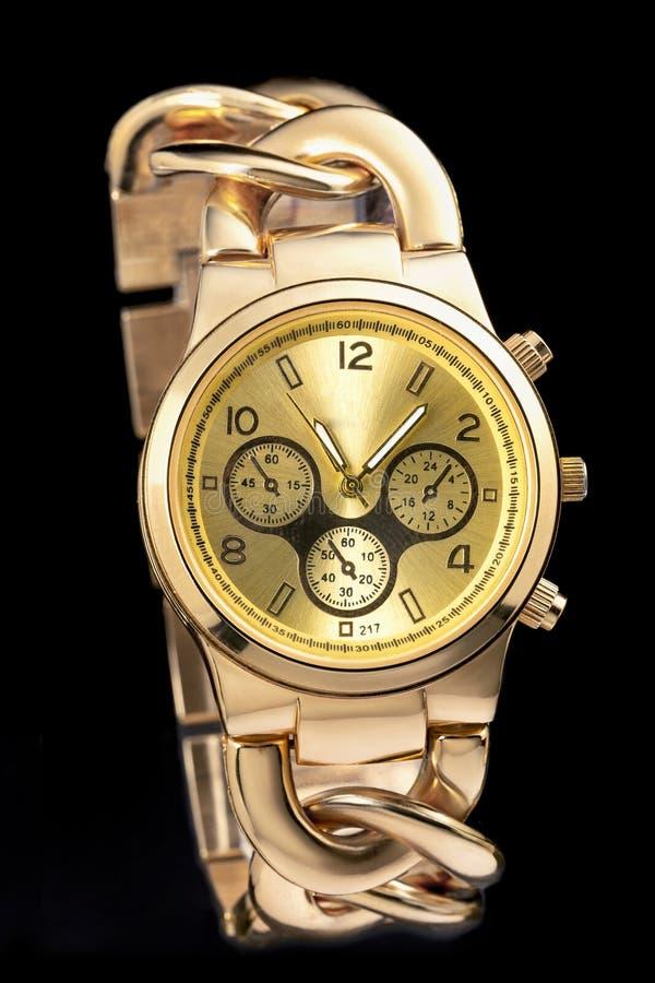 Montre-bracelet en m?tal jaune sur le fond noir photographie stock libre de droits