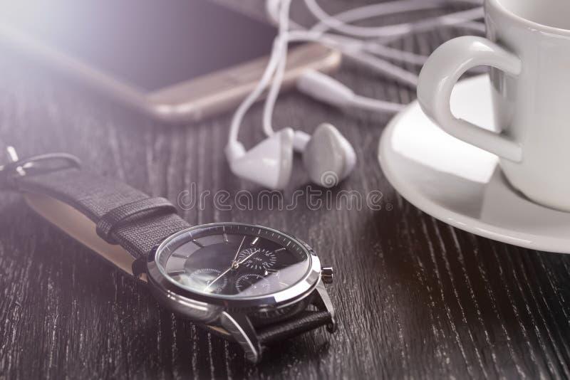 Montre-bracelet et téléphone portable avec des écouteurs et une tasse de café sur une table en bois foncée photographie stock libre de droits