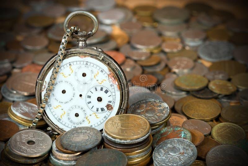 Montre de poche cassée avec de vieilles pièces de monnaie photo stock