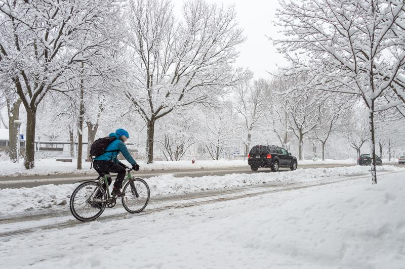 A man is riding a bicycle on a sno stock image