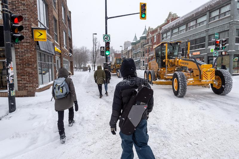 Pedestrians walking on Mont-Royal Avenue during snow storm. Montreal, Canada - 20 January 2019: Pedestrians walking on Mont-Royal Avenue during snow storm stock photography