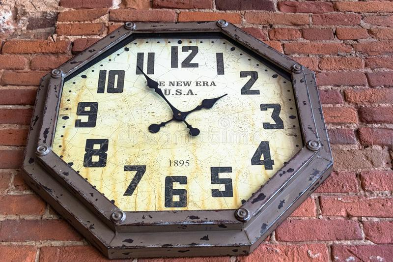 Montreal, Canada, 1895 clock on brick wall. Montreal, Canada-July 9, 2019: A `The New Era` 1895 vintage clock in a brick wall seen in the historic district of royalty free stock image