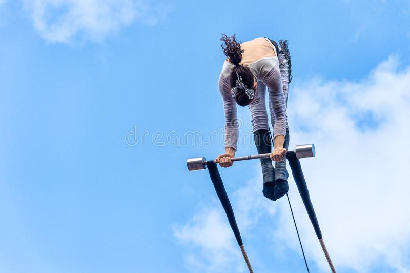 Trapeze artist performing outside. Montreal, Canada - 14 July 2018: Trapeze artist performing during Montreal Completement Cirque festival royalty free stock photography