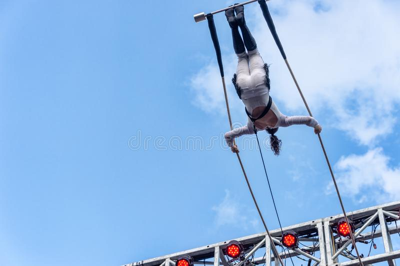 Trapeze artist performing outside. Montreal, Canada - 14 July 2018: Trapeze artist performing during Montreal Completement Cirque festival royalty free stock image