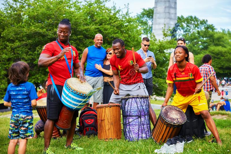 African American male and female percussionists playing djembe and dunun drums at Tam Tams festival in Mount Royal Park stock image