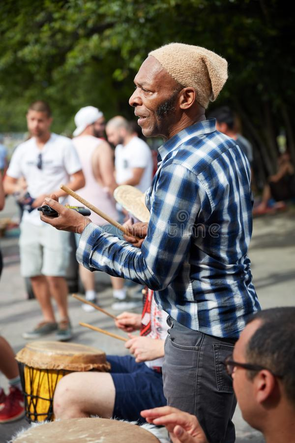 African American male percussionist playing rhythm with a cow bell at Tam Tams festival in Mount Royal Park royalty free stock photo