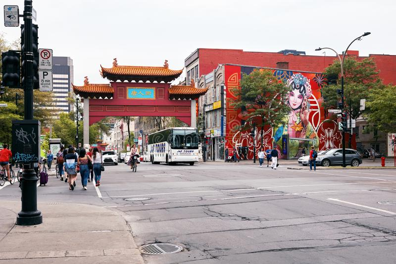 The Chinese arch gate, people and traffic at the entrance of China town on st-laurent street in Montreal, Quebec, Canada. Montreal, Canada - June 2018: The royalty free stock photos