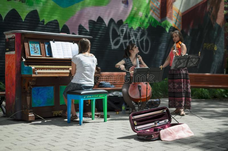 MONTREAL, CANADA, JUNE 22, 2016: Defocused view of street musicians playing outdoors at free piano in Montreal stock images
