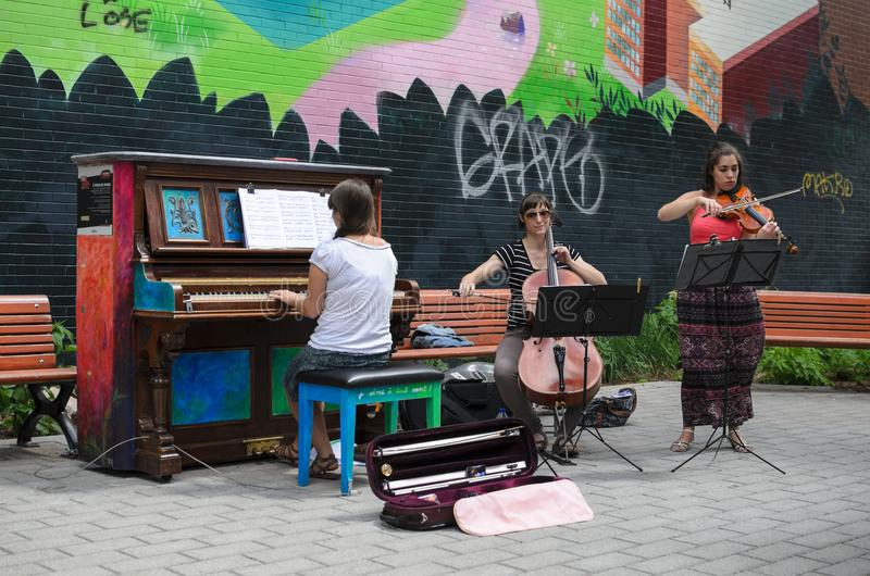 MONTREAL, CANADA, JUNE 22, 2016: Street musicians playing outdoors at free piano in Montreal stock photography