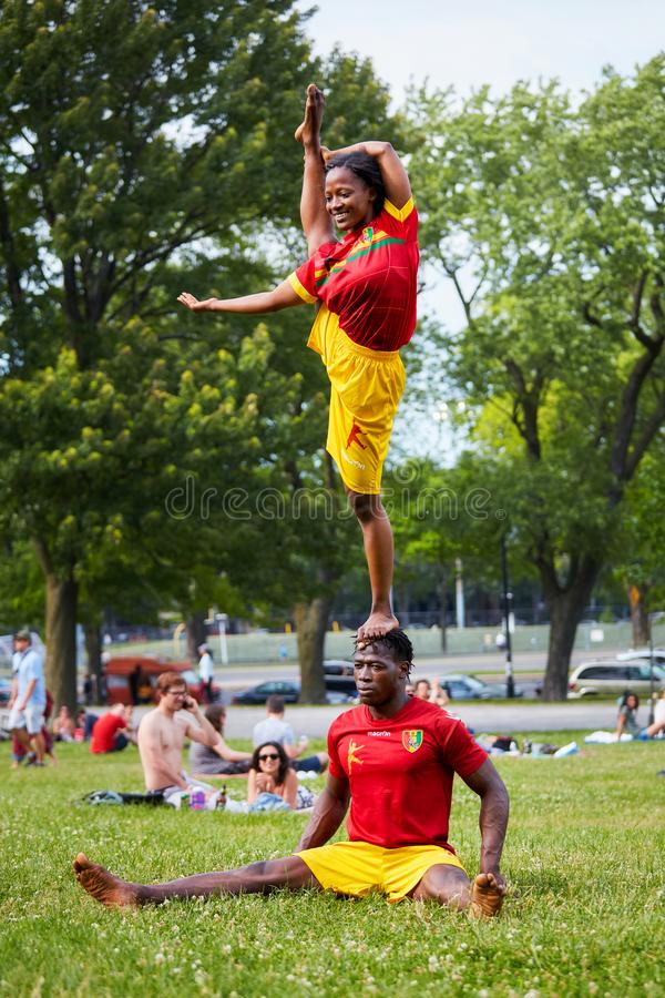 African American couple performing acrobatics show in front of the audiance in Mount Royal Park royalty free stock image