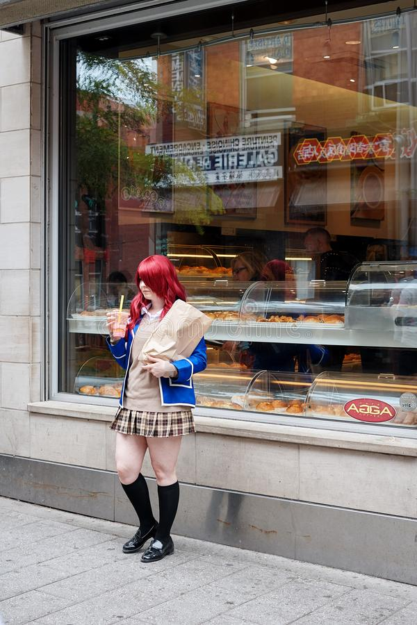 Young Asian teenage schoolgirl posing in front of a cafe stock photos