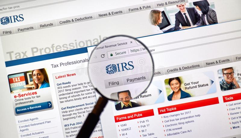 IRS web site and logo under magnifying glass. MONTREAL, CANADA - MARCH 10, 20818: IRS web site and logo under magnifying glass. The Internal Revenue Service is royalty free stock image